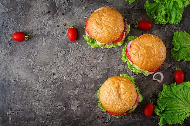 Hamburger con hamburger di carne di manzo e verdure fresche su sfondo scuro.