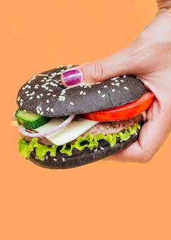 Hamburger con panino nero su sfondo arancione