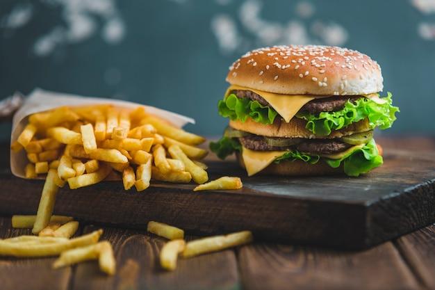 Hamburger con patate e birra scura su una tavola di legno su uno sfondo blu-grigio