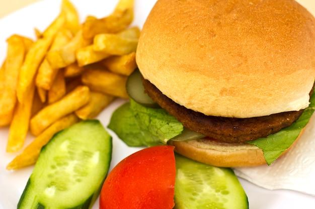 Hamburger con patatine fritte, cetrioli a fette e pomodori