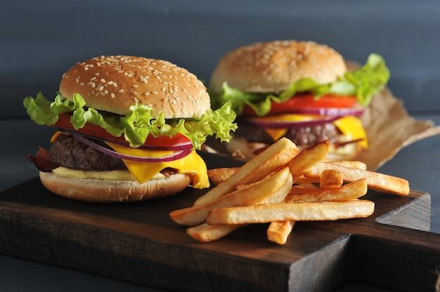 Hamburger con patatine fritte su tavola di legno rustico