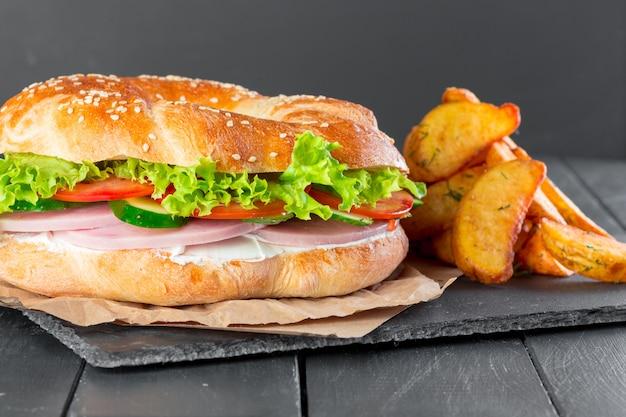 Hamburger con patatine fritte su un piatto di ardesia