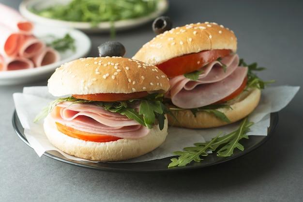 Hamburger con prosciutto due hamburger, cibo avariato. panino sano con verdure fresche.