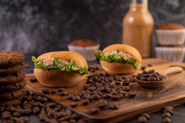 Hamburger con tagliere in legno, inclusi cupcakes e chicchi di caffè.
