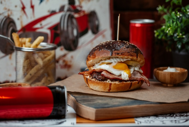 Hamburger con uovo alla benedict e lattine di bevande energetiche