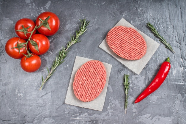 Hamburger crudi su carta pergamena con pomodori, peperoncino e rosmarino.