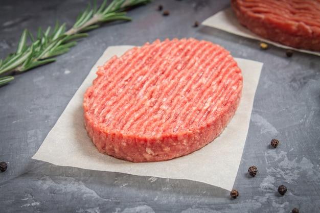 Hamburger crudi su carta pergamena con rosmarino. sfondo di marmo grigio.