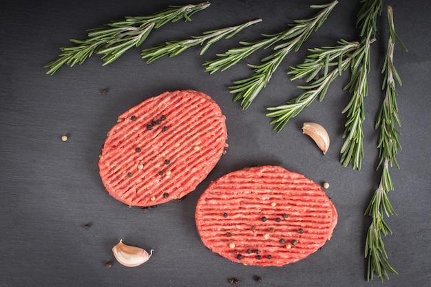 Hamburger crudi su una tavola di ardesia con rosmarino e aglio. sfondo di legno marrone.