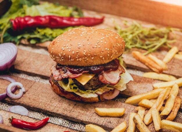 Hamburger del bacon con manzo e le patate fritte sulla tavola di legno