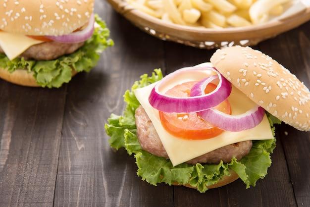 Hamburger del bbq con le patate fritte sulla tavola di legno.