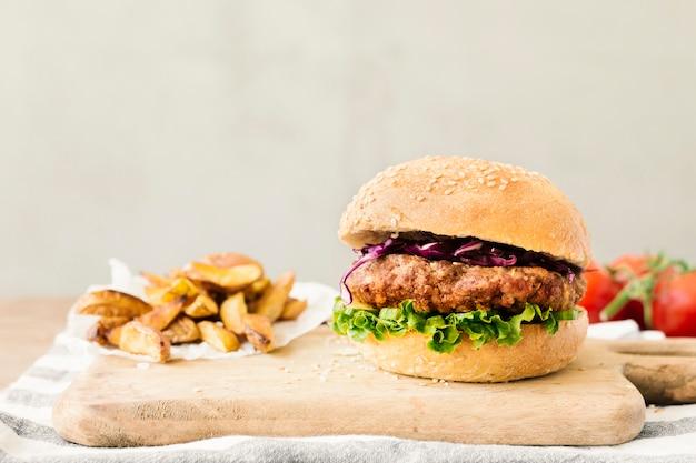 Hamburger del primo piano dell'angolo alto con le fritture sul bordo di legno