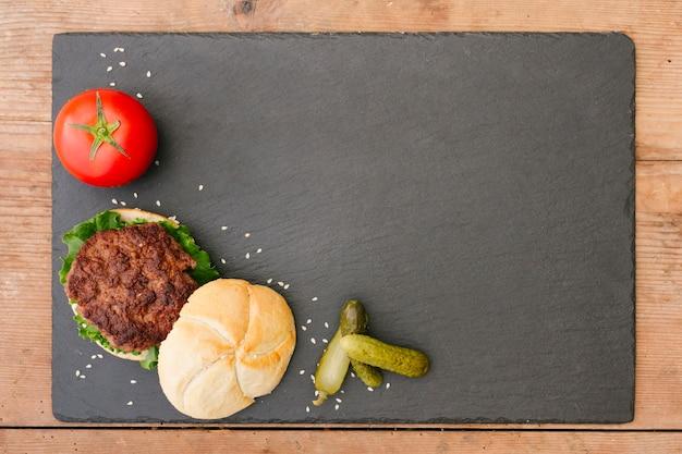 Hamburger del primo piano dell'angolo alto con le fritture sul piatto