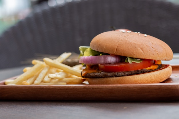 Hamburger deliziosi con formaggio e patatine fritte.