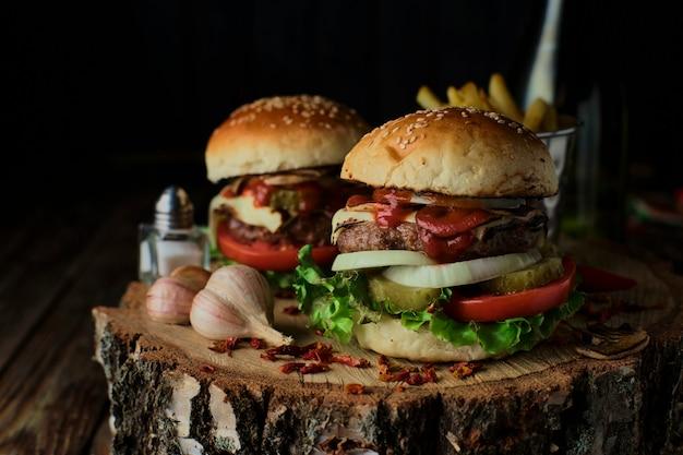 Hamburger deliziosi in stile rustico su fondo di legno scuro.