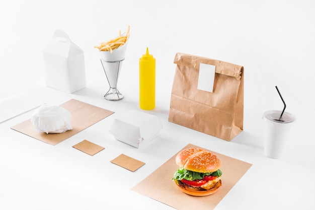 Hamburger delizioso; pacchi; tazza di smaltimento e bottiglia di salsa su sfondo bianco