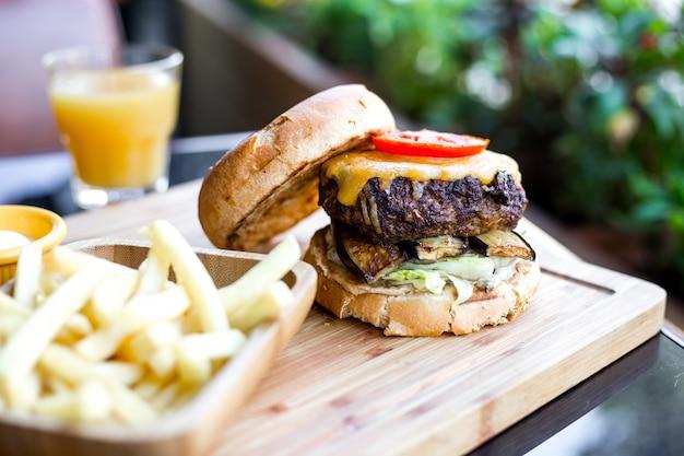 Hamburger della carne con la vista laterale del pomodoro del formaggio della melanzana della lattuga