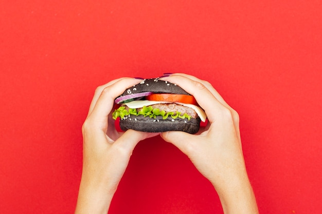Hamburger della tenuta della donna sopra la tavola rossa