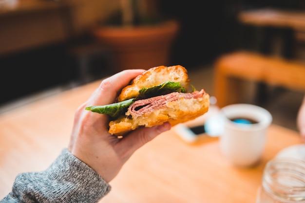 Hamburger della tenuta della persona con lattuga e il pomodoro