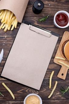 Hamburger di alto angolo con patatine fritte accanto a cliboard
