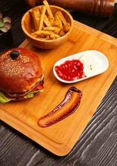 Hamburger di carne di pollo con pomodoro e lattuga all'interno e patatine fritte servite con olive nere e ketchup su un vassoio di legno