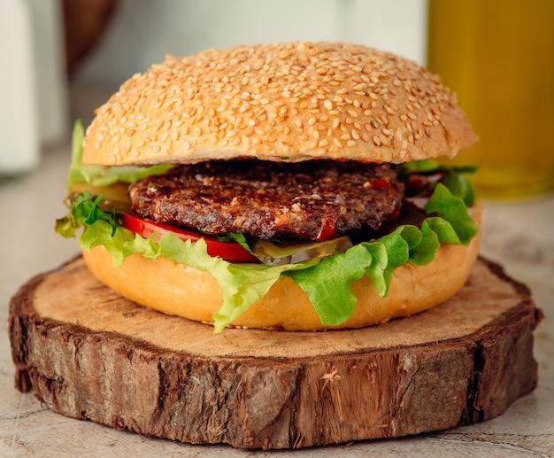 Hamburger di carne grande su tavola di legno