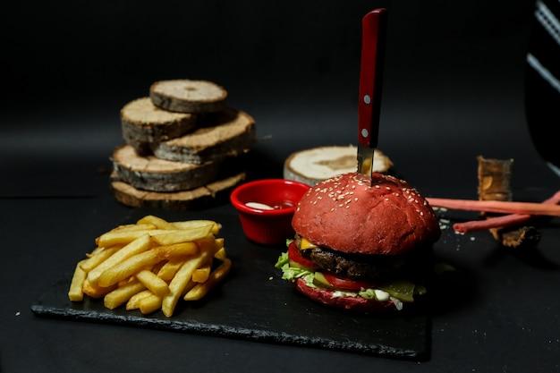 Hamburger di carne vista frontale con patatine ketchup e maionese su un supporto con un coltello