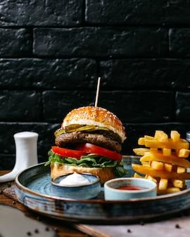 Hamburger di carne vista laterale con ketchup di patatine fritte e maionese sul vassoio