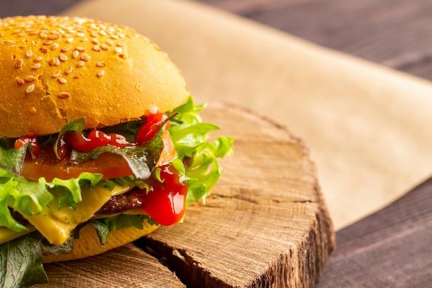 Hamburger di fast food di strada con manzo, formaggio, lattuga, pomodoro in un panino bianco con sesamo