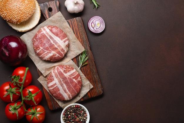 Hamburger di ingredienti cotoletta cruda, pomodori, lattuga, panino, formaggio, cetrioli e cipolla