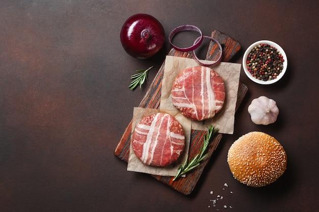 Hamburger di ingredienti cotolette crude, lattuga, panino e cipolla