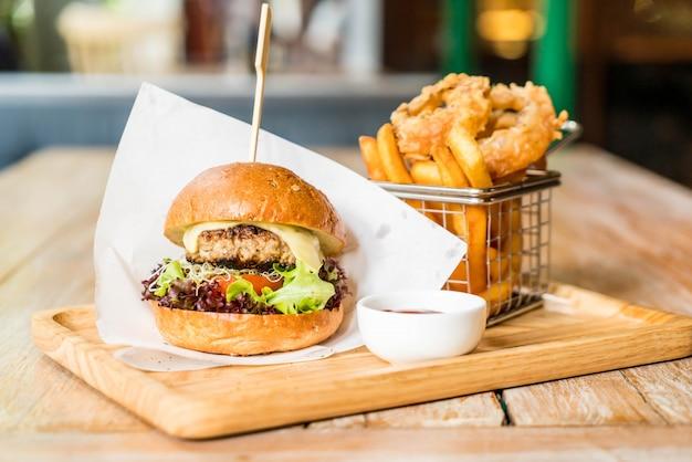Hamburger di maiale con anelli di cipolla e patate fritte