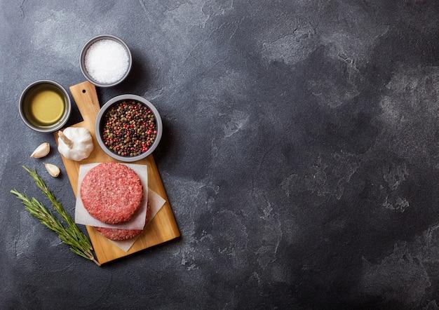Hamburger di manzo alla griglia macinati crudi fatti in casa con spezie ed erbe aromatiche. vista dall'alto. in cima al tagliere e al tavolo della cucina. con pepe sale e olio.