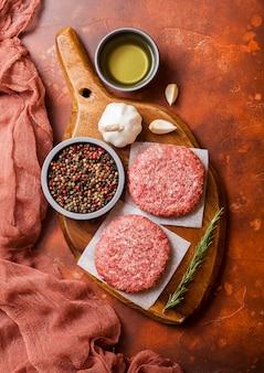 Hamburger di manzo alla griglia macinati crudi fatti in casa con spezie ed erbe aromatiche. vista dall'alto. in cima al tagliere e alla cucina arrugginita. con pepe sale e aglio.