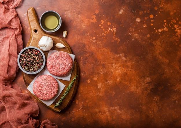 Hamburger di manzo alla griglia macinati crudi fatti in casa con spezie ed erbe aromatiche. vista dall'alto. in cima al tagliere e alla cucina arrugginita. con pepe sale e olio.