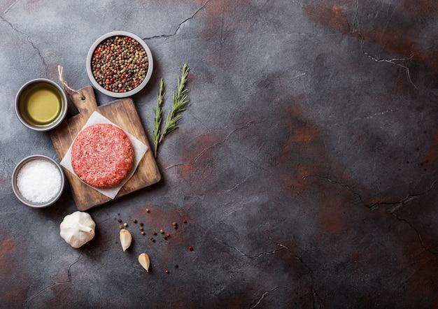 Hamburger di manzo alla griglia macinati crudi fatti in casa con spezie ed erbe aromatiche. vista dall'alto. in cima al tagliere e alla cucina. con pepe sale e olio.