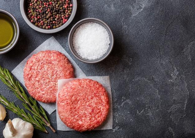 Hamburger di manzo alla griglia macinati crudi fatti in casa con spezie ed erbe aromatiche. vista dall'alto. pepe, sale e olio in cucina.