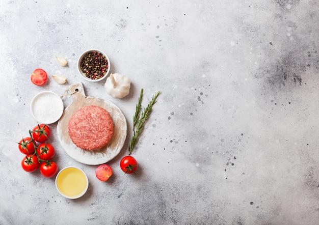 Hamburger di manzo alla griglia tritato crudo con spezie ed erbe aromatiche. vista dall'alto. sulla parte superiore del tagliere bianco e cucina. con pepe sale e aglio.