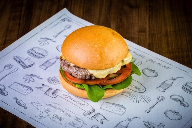 Hamburger di manzo artigianale con formaggio e rucola foglie sul tavolo di legno