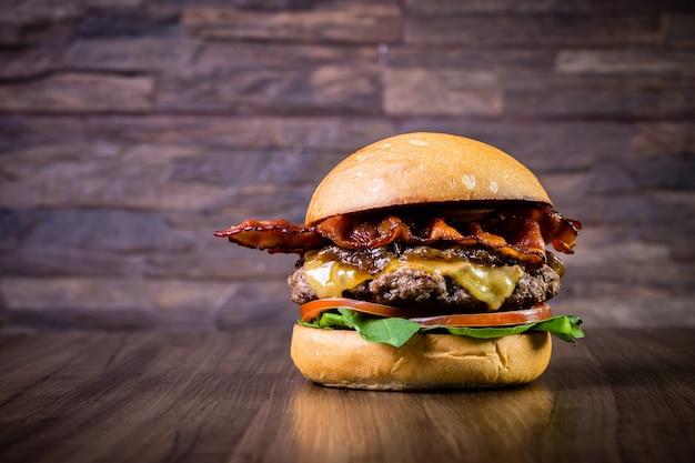 Hamburger di manzo artigianale con formaggio, pancetta, cipolla caramellata e foglie di rucola sul tavolo di legno