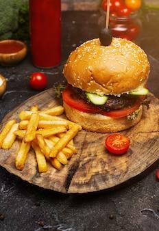 Hamburger di manzo fresco gustoso e patatine fritte su tavola di legno, ketchuo, pomodori, verdure