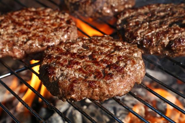 Hamburger di manzo per hamburger sulla griglia a fiamma del barbecue