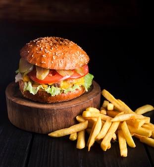 Hamburger di manzo pronto per essere servito con patatine fritte