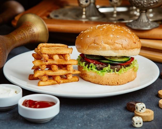 Hamburger di manzo servito con patatine fritte, maionese e ketchup