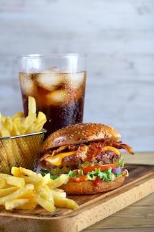 Hamburger di pancetta e formaggio con patatine fritte e un bicchiere di cola