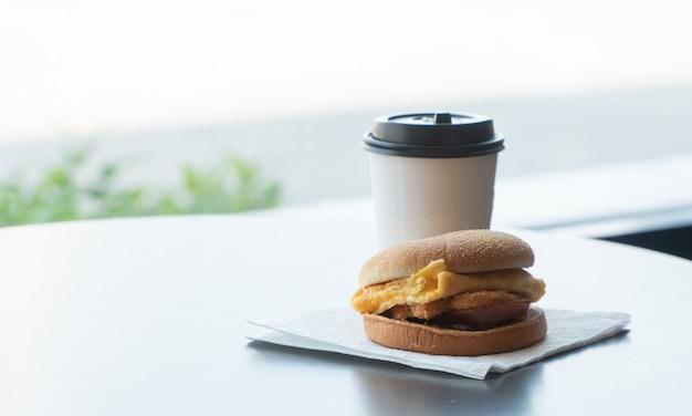 Hamburger di pancetta e frittata sulla carta con la tazza di caffè di carta bianca sul tavolo nel ristorante fast food