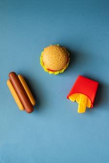 Hamburger di plastica, insalata, pomodoro, patate fritte con un hot dog su sfondo blu