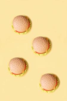 Hamburger di plastica, insalata, pomodoro, su uno sfondo giallo