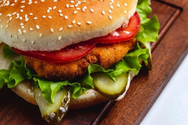 Hamburger di pollo vista laterale con pomodoro a fette e lattuga sul bordo