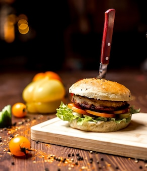 Hamburger di pollo vista laterale con tortino di pollo pomodoro pomodoro foglia di lattuga in panini hamburger e pepe nero sul tavolo