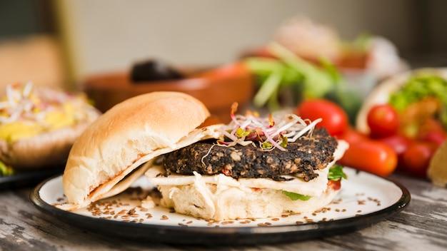 Hamburger di quinoa vegetariano con germogli e semi di lino sul piatto bianco
